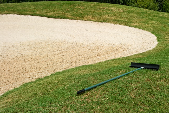 Newly raked sand trap at a golf course with the rake lying in the green grass beside it.