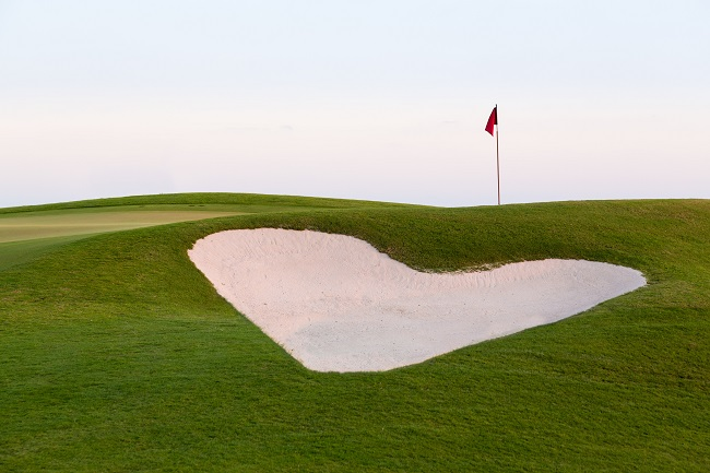 Heart shaped sand bunker in front of red flag of golf hole on beautiful course at sunset illustrating love for game of golf